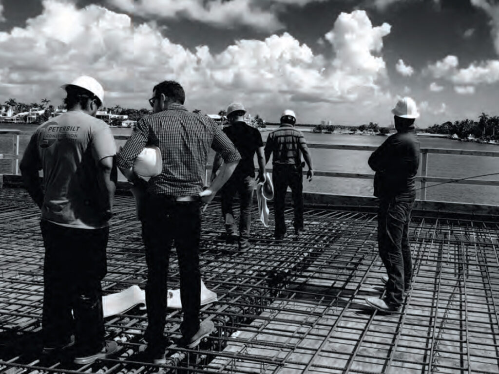 Group of contractors in hard hats looking at blue prints on the unfinished roof of a building