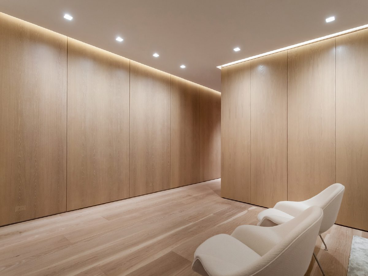 Continuum North Miami private residence open living room with light wood walls and floor