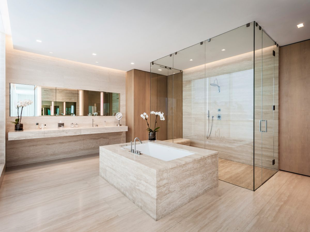 Continuum North Miami private residence bathroom, with light marble tub and floors